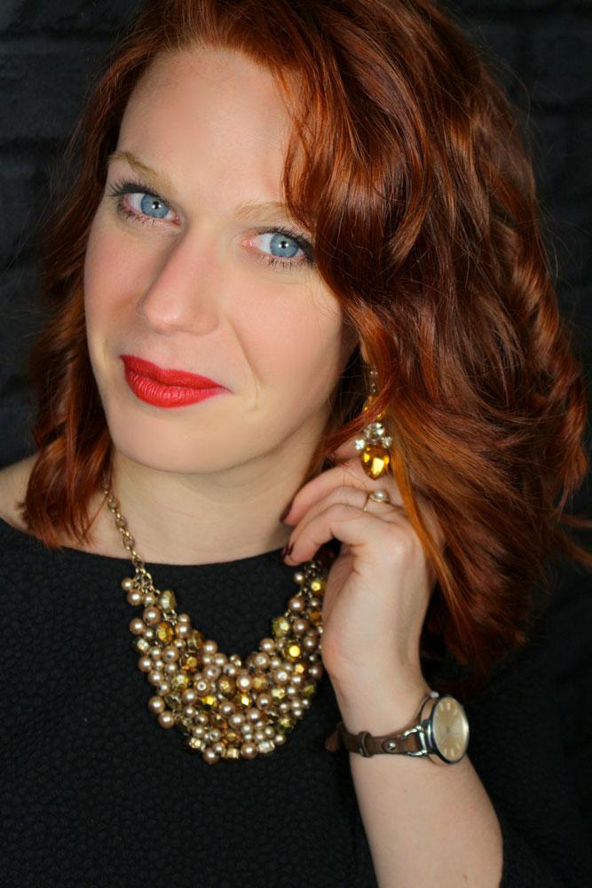 Zoom sur Sandie avec ses bijoux dorés, ses yeux bleus, son rouge à lèvres rouge et ses cheveux roux