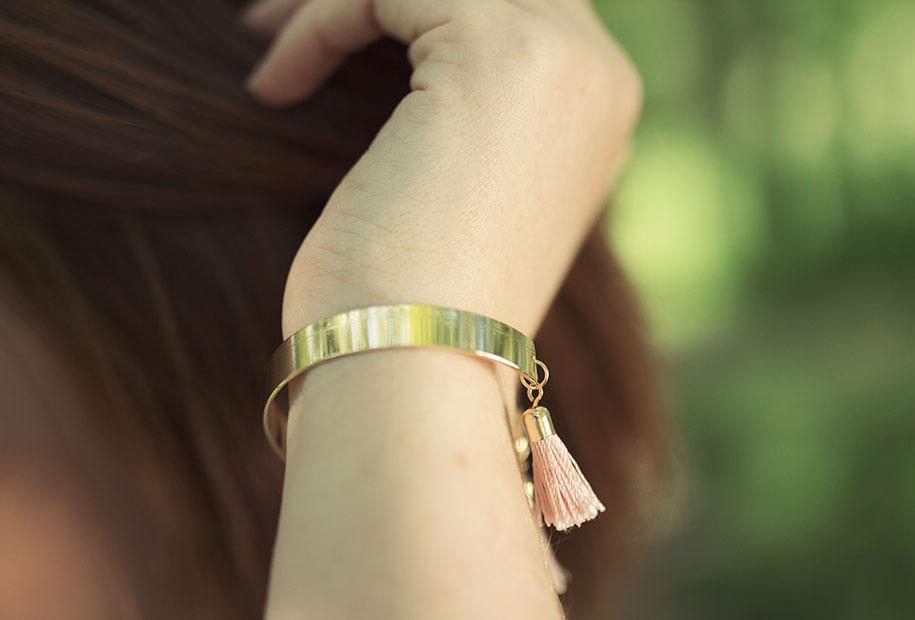 Zoom sur le bracelet doré à pompoms rose de la marque MOA