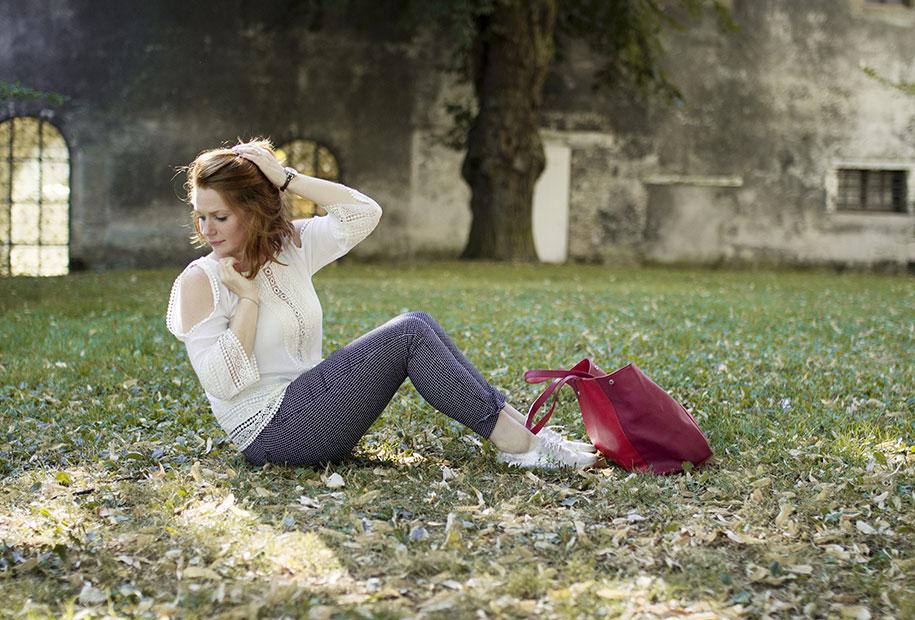 Look de rentrée en pantalon, blouse aux épaules dénudées, chaussures argentées et sac rouge