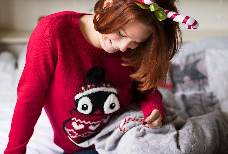 Sous un plaid, au chaud dans un pull de Noël, un sucre d'orge à la main, pour le TAG de Noël