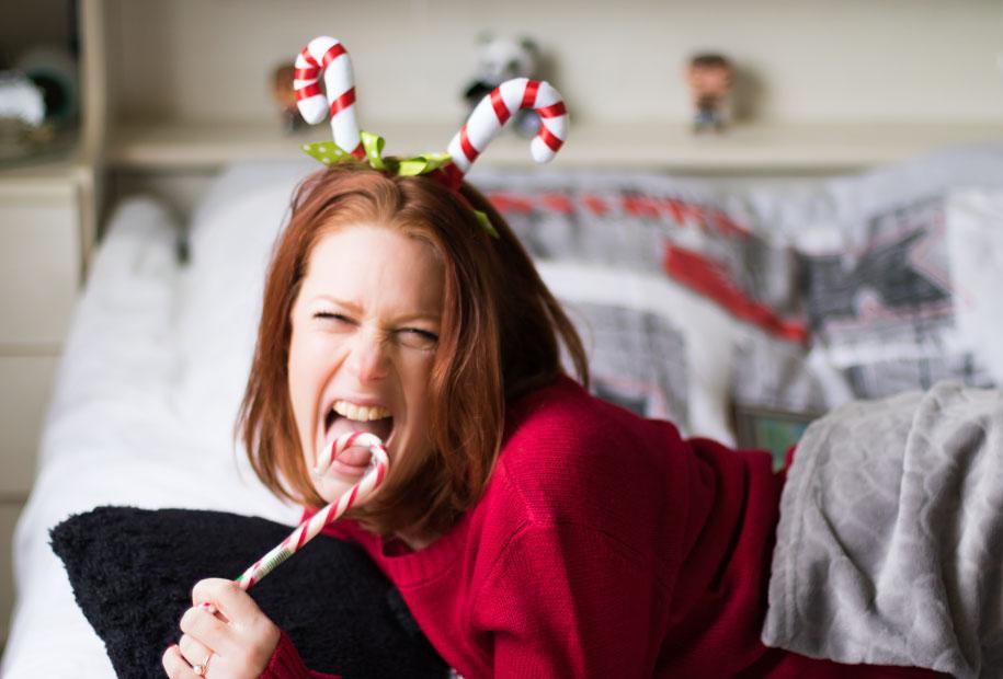 Prête à manger un délicieux sucre d'orge, sous un plaid au chaud dans un pull de Noël pour le TAG de Noël