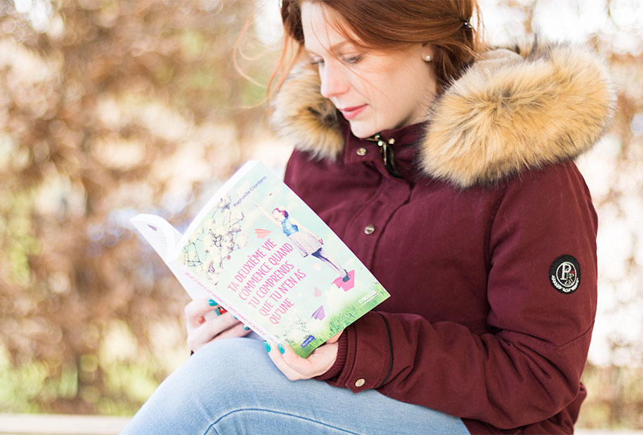 Au soleil, en pleine lecture du livre Ta deuxième vie commence quand tu comprends que tu n'en as qu'une