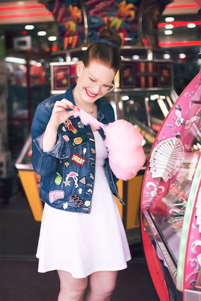 Look en robe patineuse blanche et veste en jean à pin's à la fête foraine près des machine à sous avec la barbe à papa