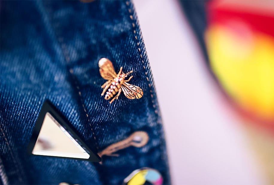 Zoom sur le pin's abeille accroché à la veste en jean du look à la fête foraine de Tours