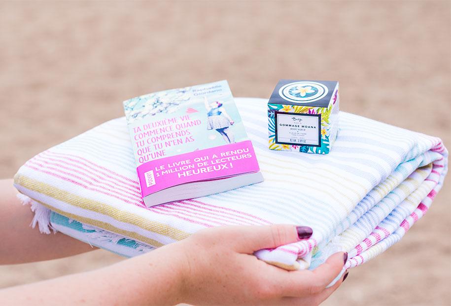 Zoom sur les cadeaux du concours pour le 100ème article, un drap de plage coloré Eurodif, un livre de Raphaëlle Giordano et le gommage à la fleur de Tiaré Baïja
