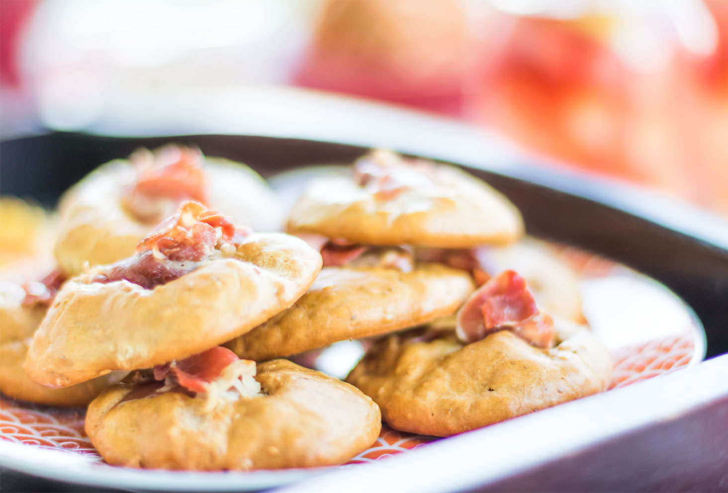 Recette de l'été, les cookies salés aux graines de sésame et jambon de parme dans une assiette Zodio orange et blanche