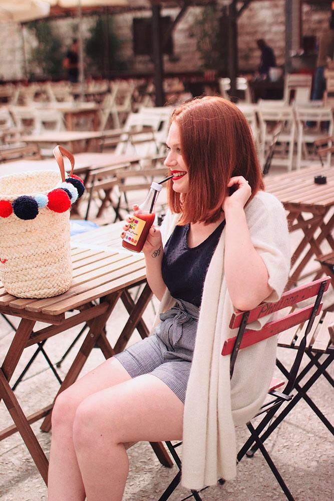 Look Harris Wilson avec un panier à pompons à la guinguette de Tours sur les bords de Loire, assise à une table avec un jus de fraise