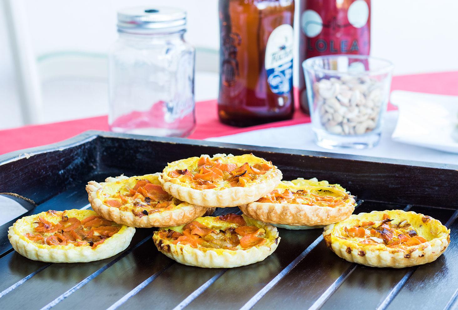 Ensemble des tartelettes aux carottes et curry avec un fond de Vache Qui Rit, pour les recettes de l'été, présentées sur un grand plateau