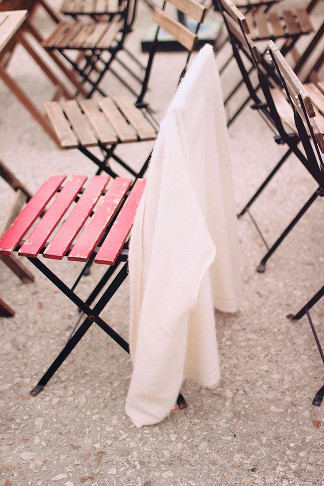 Zoom sur le gilet blanc Harris Wilson accroché à une chaise rouge de la guinguette de Tours sur les bords de Loire