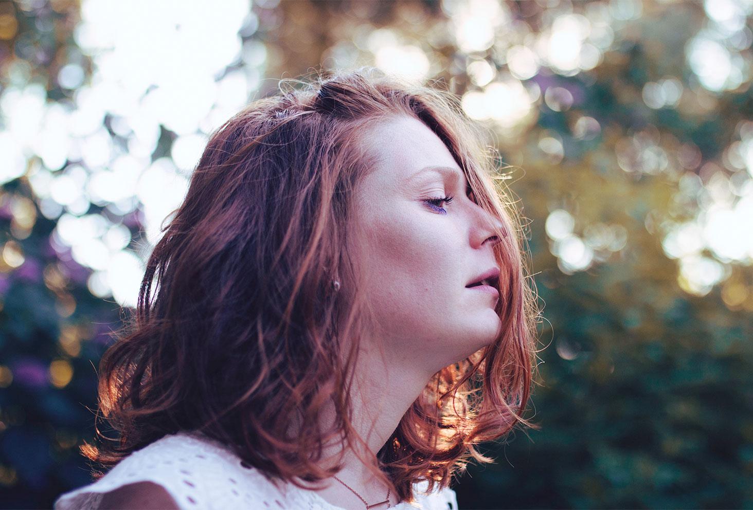 Portrait cheveux bouclés et maquillage bleu dans le look en robe blanche en dentelle et dos nu