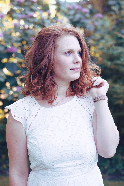 Cheveux bouclés et parfaite robe blanche en dentelle et dos nu