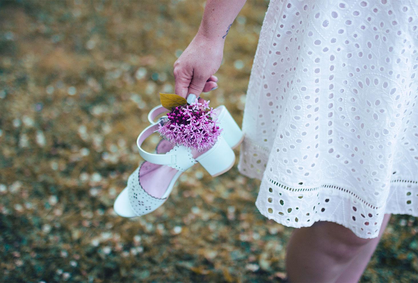 Zoom sur la dentelle de la robe blanche et sur les sandales à talons mint