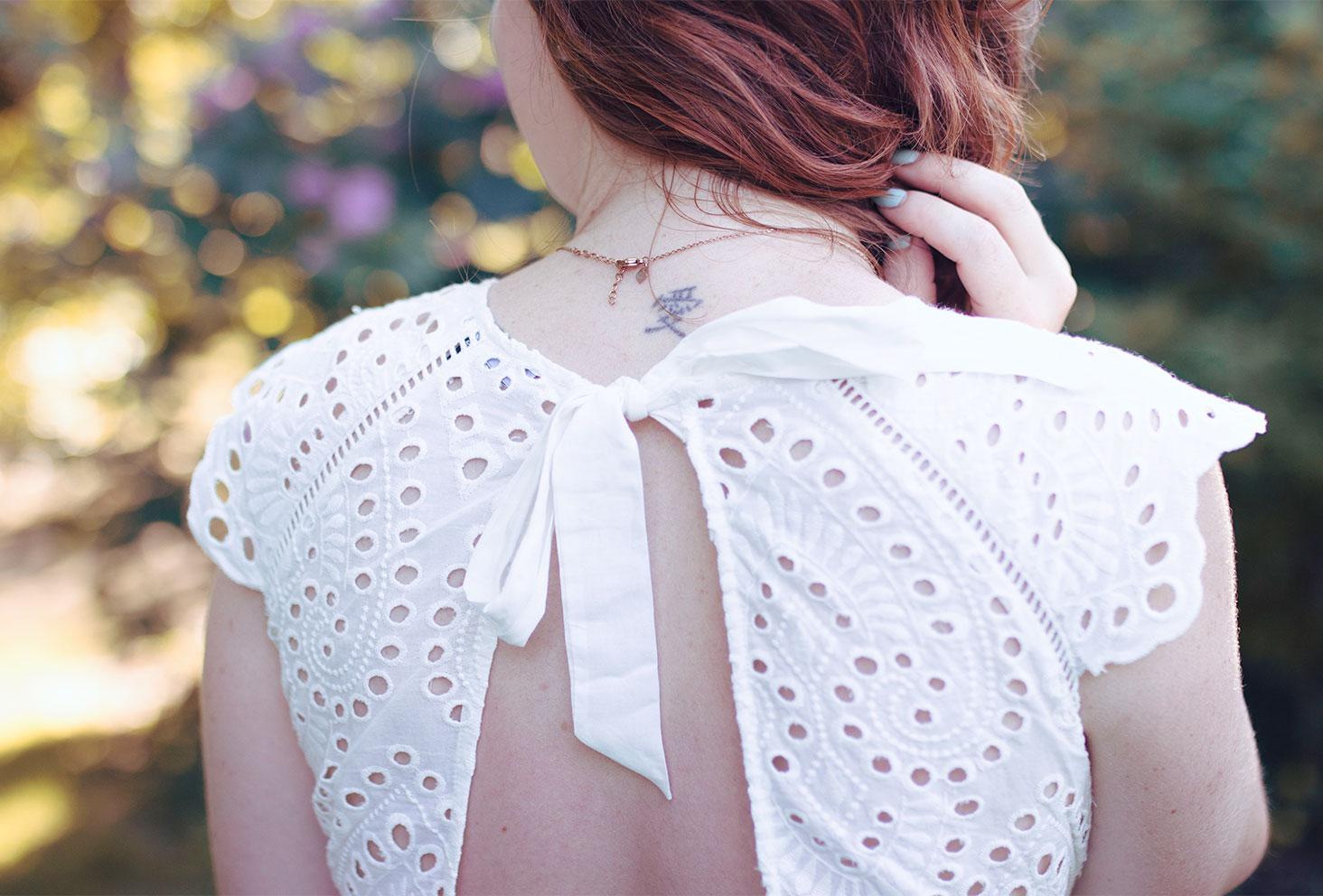 Zoom sur le dos nu de la robe blanche en dentelle de chez ETAM