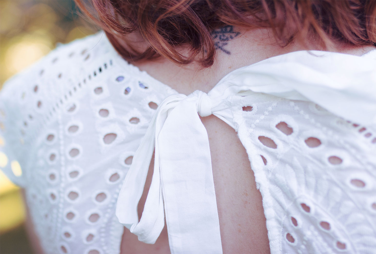 Zoom sur le noeud du dos nu de la robe blanche en dentelle ETAM
