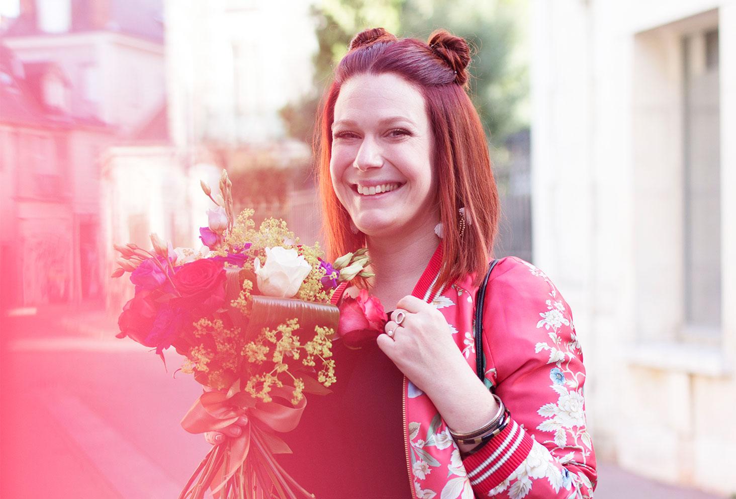 Zoom visage et bouquet de fleurs dans le look du bomber à fleurs