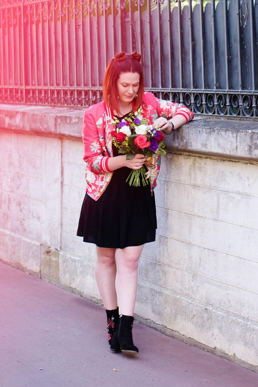 Look entier du bomber à fleurs accoudée au mur