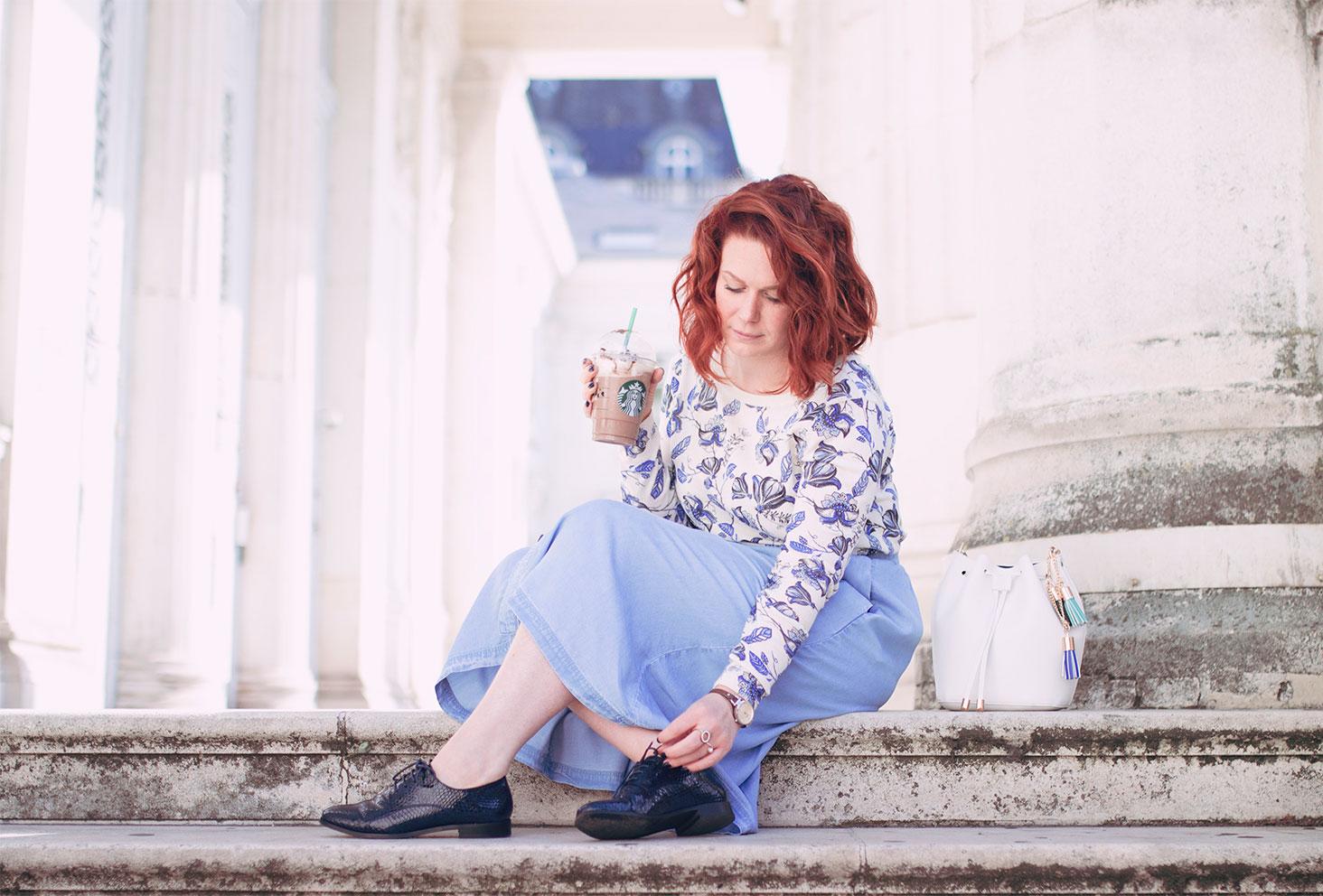 Assise dans les marches avec une jupe midi en jean, un pull à fleurs, des derbies vernis bleu et un Starbucks pour la rentrée