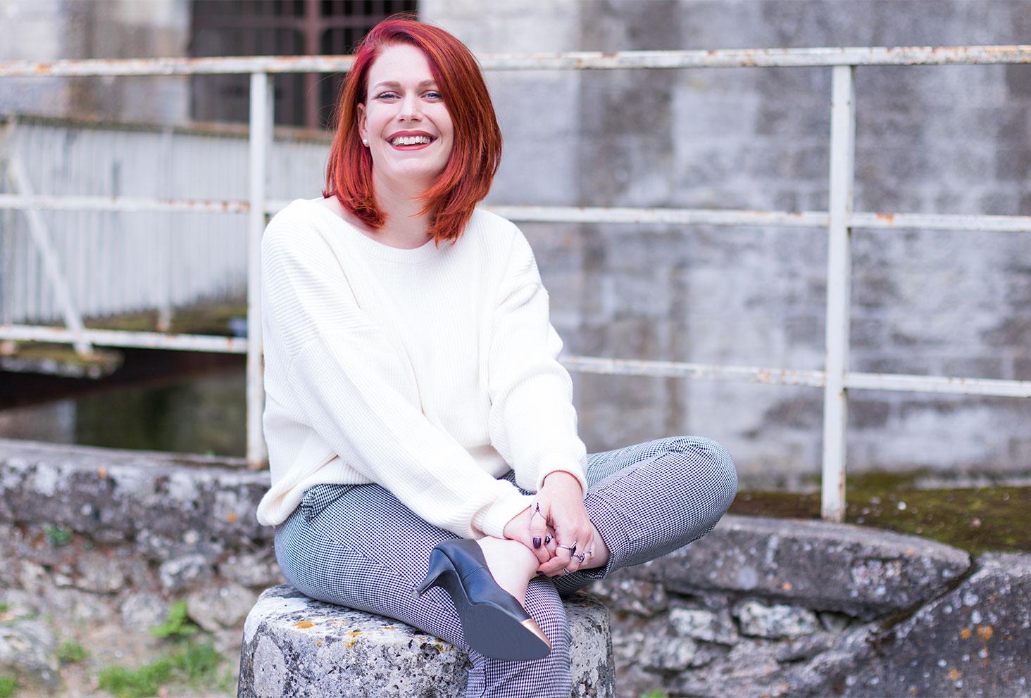 Assise sur la pierre devant le château d'amboise pour le look de la rentrée en pantalon pied-de-poule et pull blanc Zara
