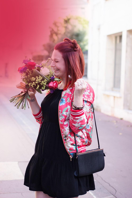Zoom sur la robe à volants noires et bomber à fleurs Promod