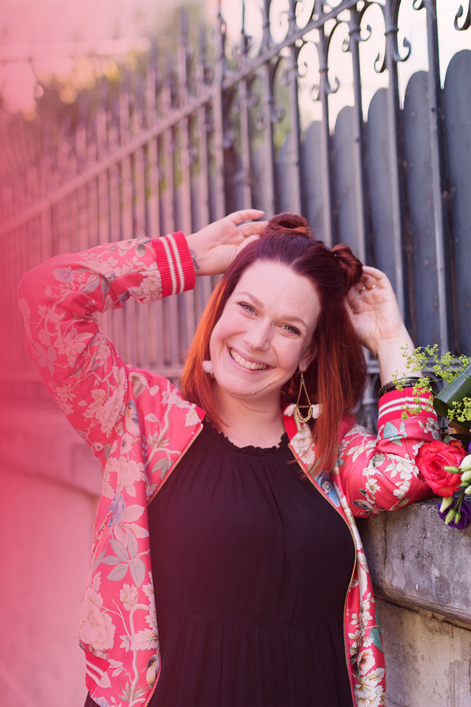 Zoom sur le bomber rouge à fleurs Promod et la coiffure pompons