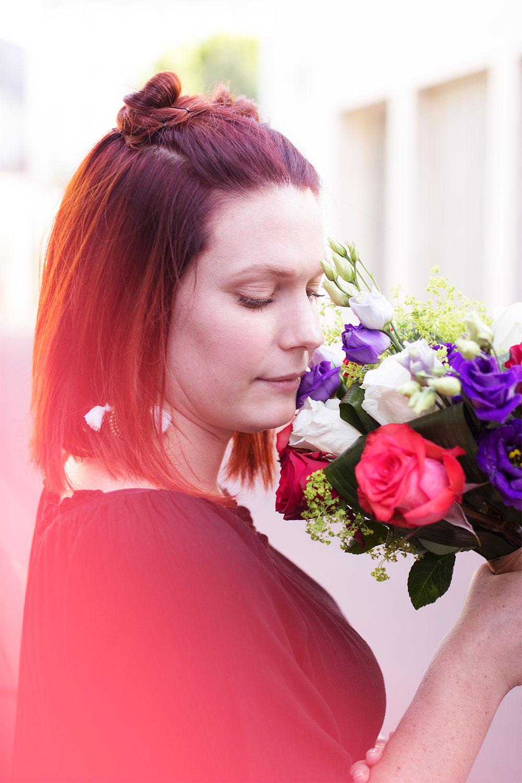 Zoom visage et bouquet du look en bomber à fleurs rouges