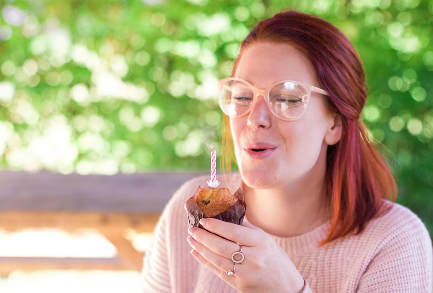 Souffle de la bougie sur muffin pour anniversaire des 26 ans