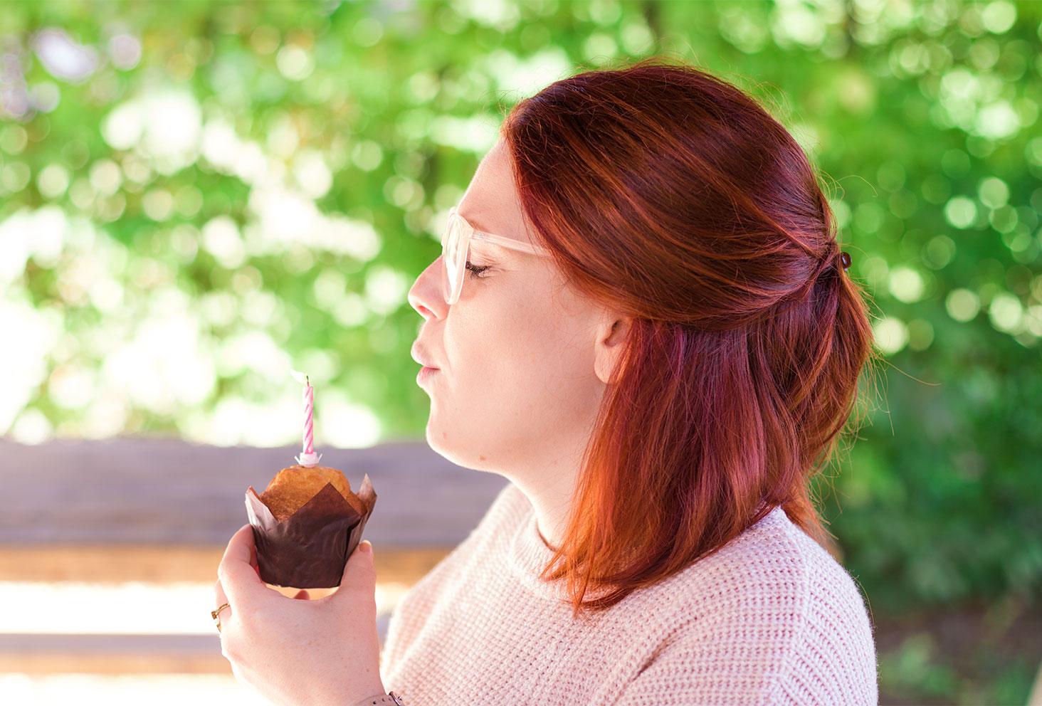 Souffle de la bougie sur le muffin pour l'anniversaire des 26 ans