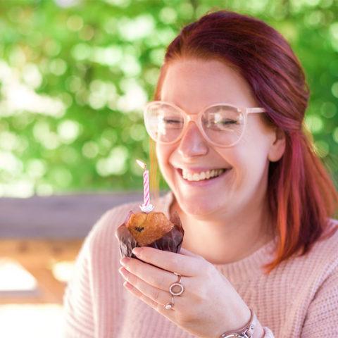 Sourire avant du souffle de la bougie sur le muffin pour l'anniversaire des 26 ans