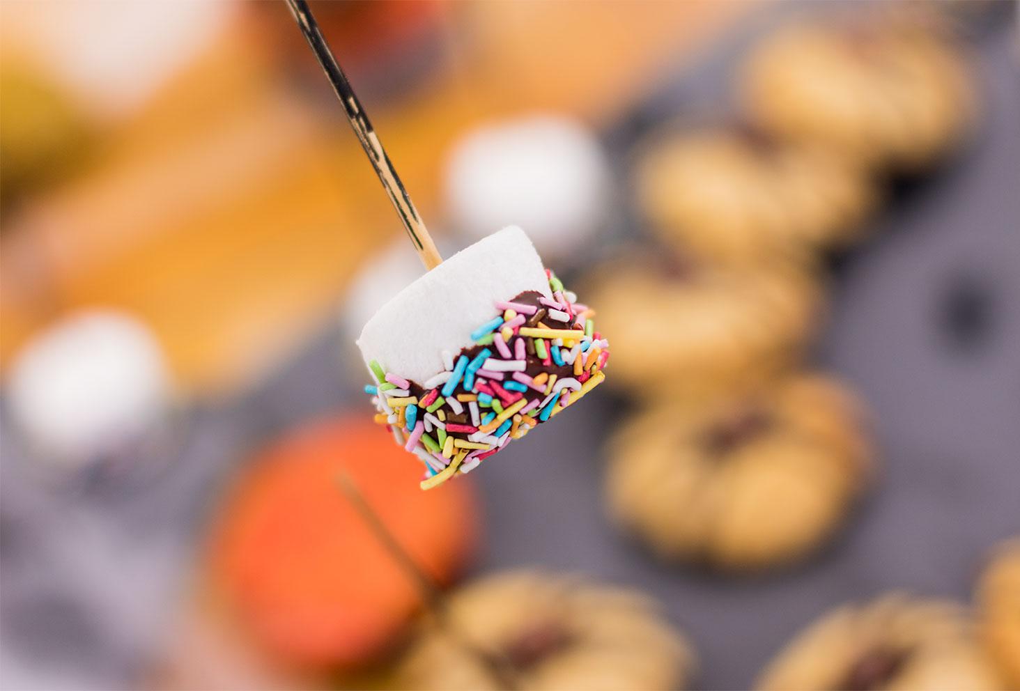 Zoom sur un chamallow enrobé de chocolat en forme de balais de sorcière pour le goûter d'Halloween