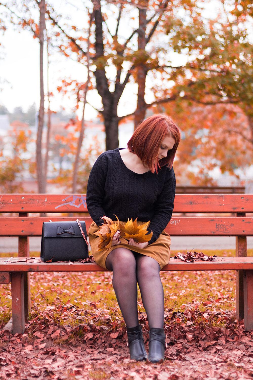 Assise sur le banc pour le look Modz au milieu des couleurs automnales avec des feuilles dans les mains