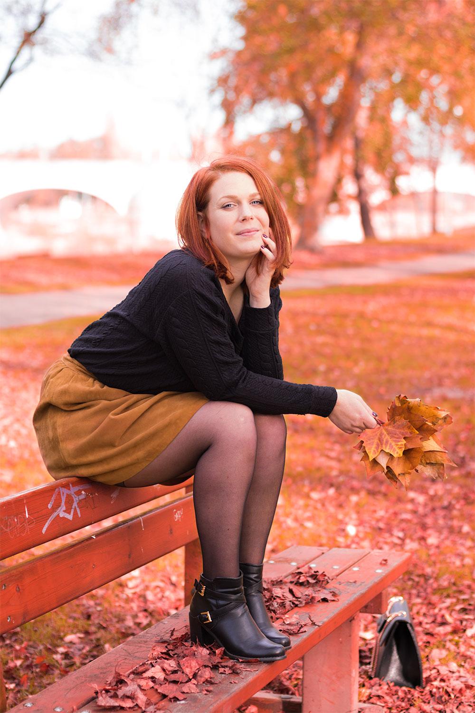 Look Modz assise sur un banc au milieu des couleurs automnales avec des feuilles dans les mains.