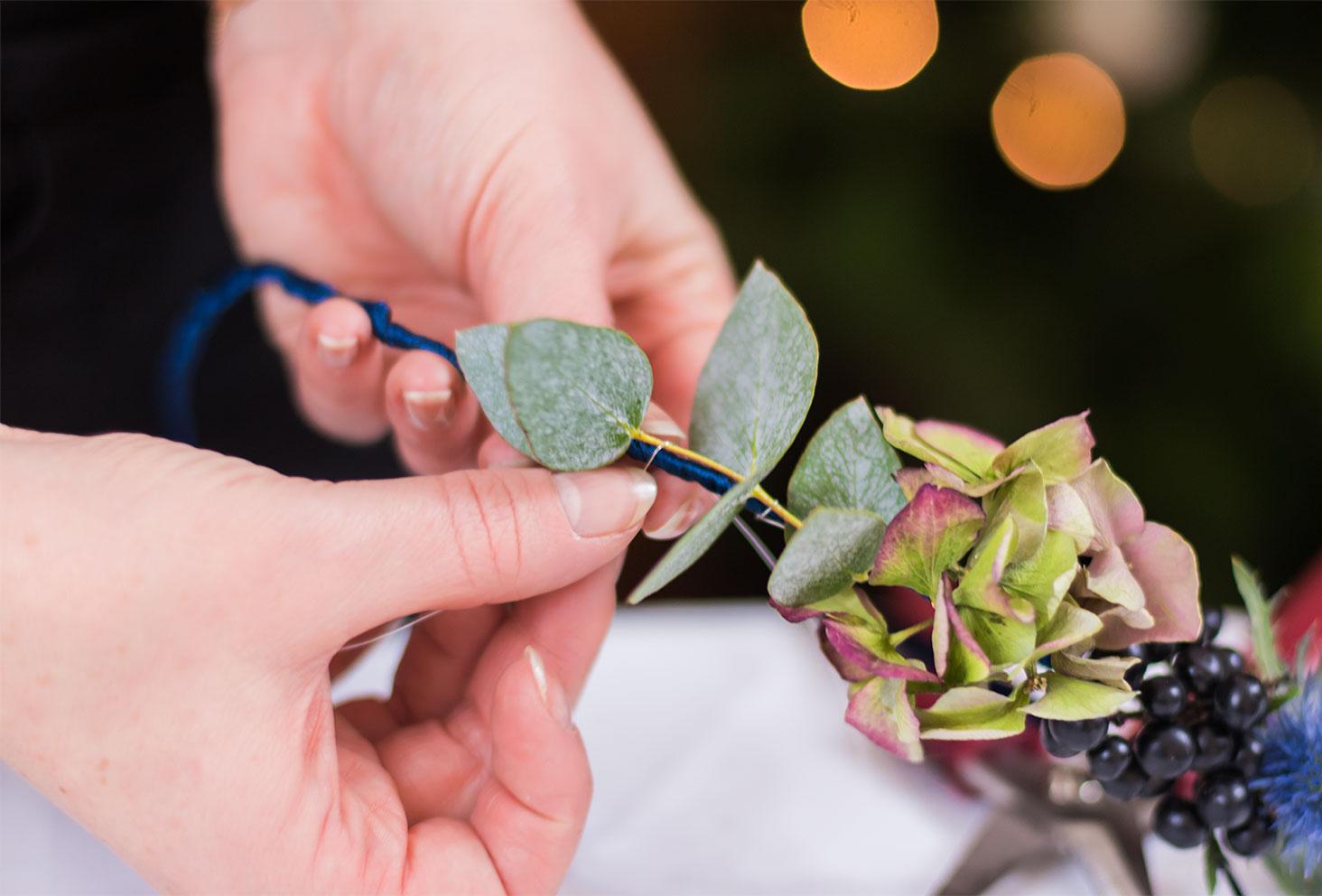 Zoom sur la fixation de l'eucalyptus sur la couronne de fleurs