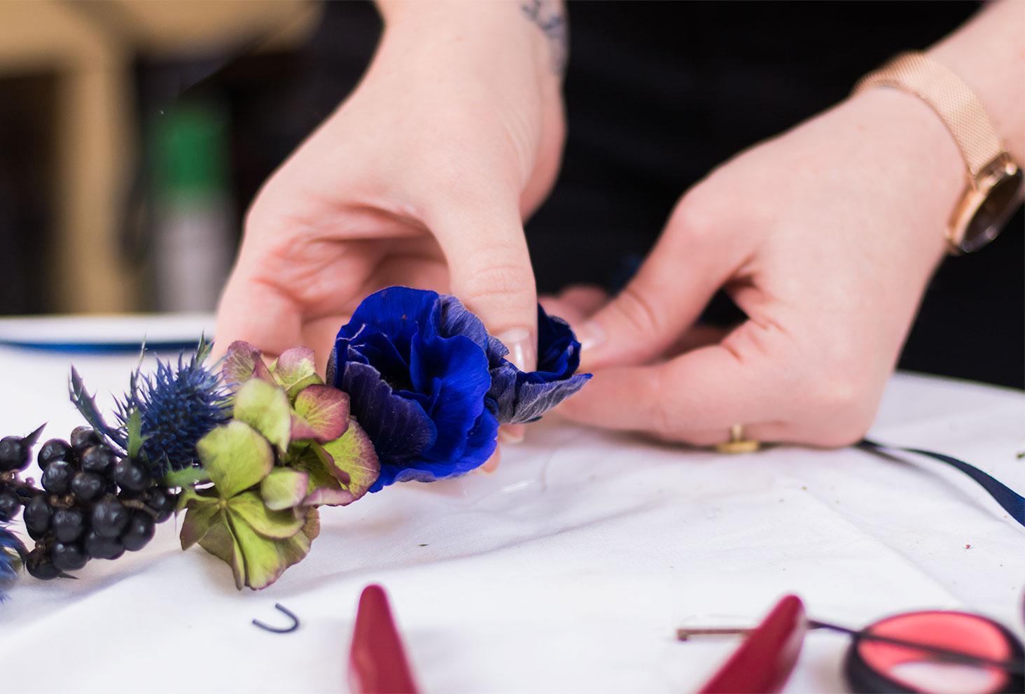 Zoom sur le collage d'une anémone bleu sur la couronne de fleurs