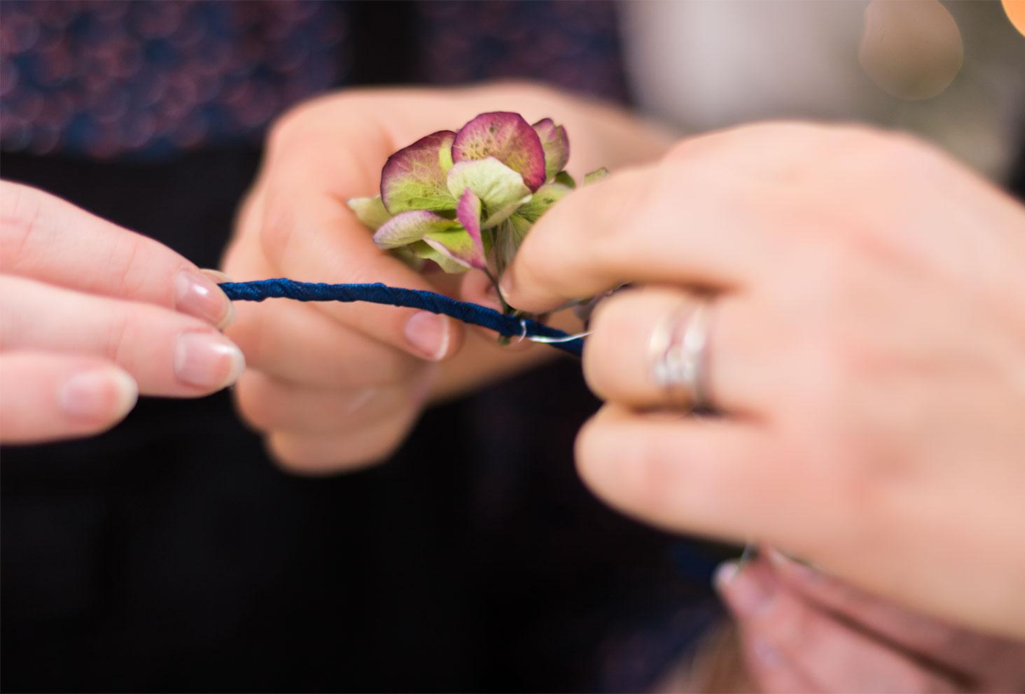 Zoom sur la fixation d'un hortensia sur la couronne de fleurs