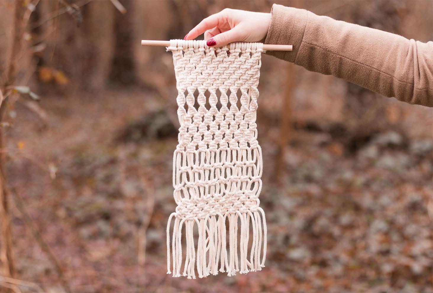 Macramé en fil de coton beige sur une suspension en bois tenu par une main au milieu de la forêt