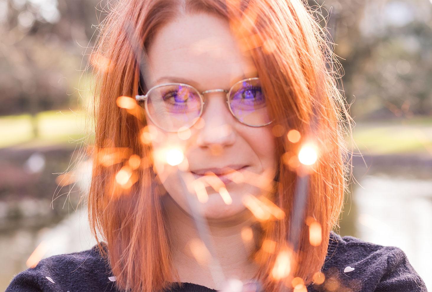Visage de Sandie avec ses lunettes derrière une bougie magique pour la nouvelle année