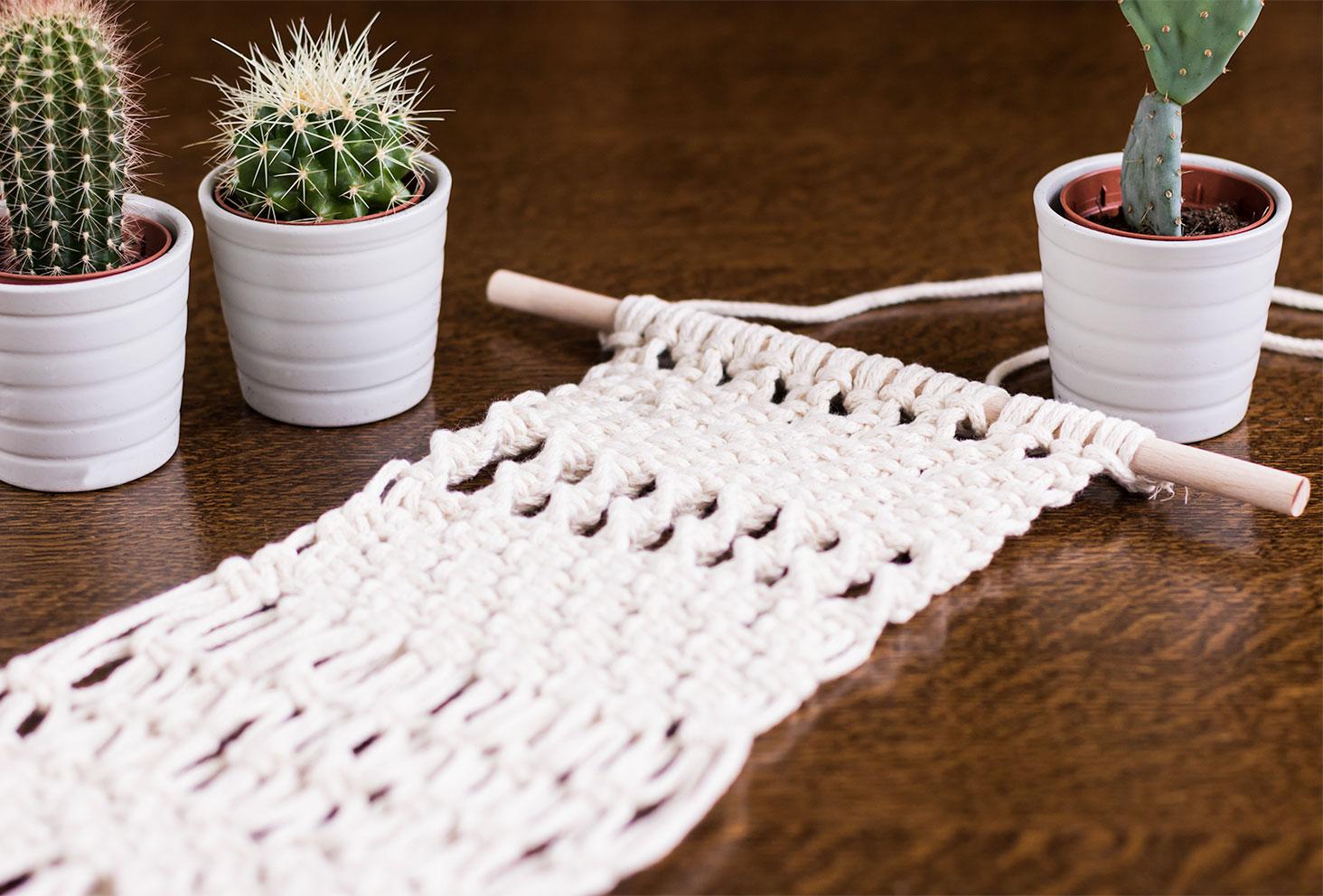 Macramé beige posé sur une table en bois entouré de cactus