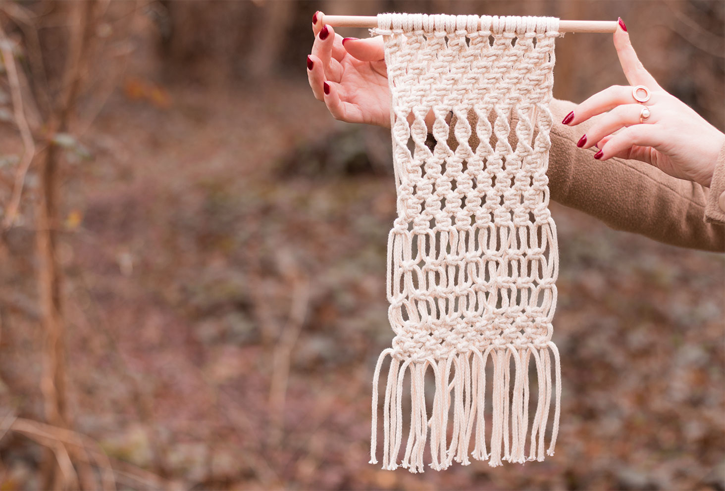 Macramé beige accroché à une suspension en bois tenu entre deux doigts au milieu de la forêt