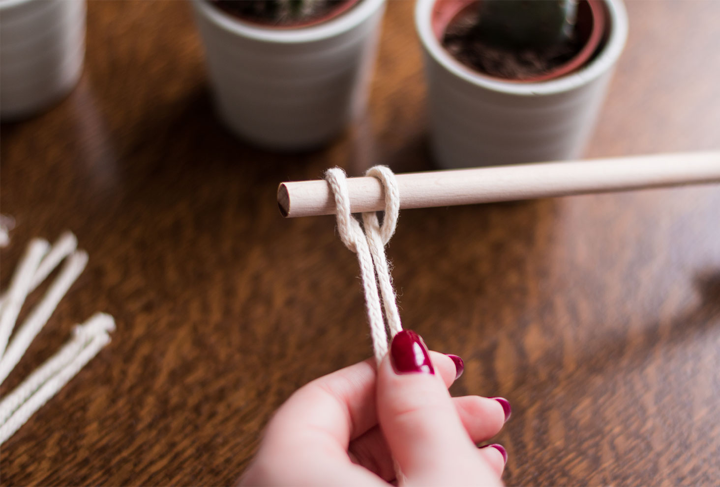 Zoom sur un noeud de montage accroché à la barre en bois d'un futur macramé