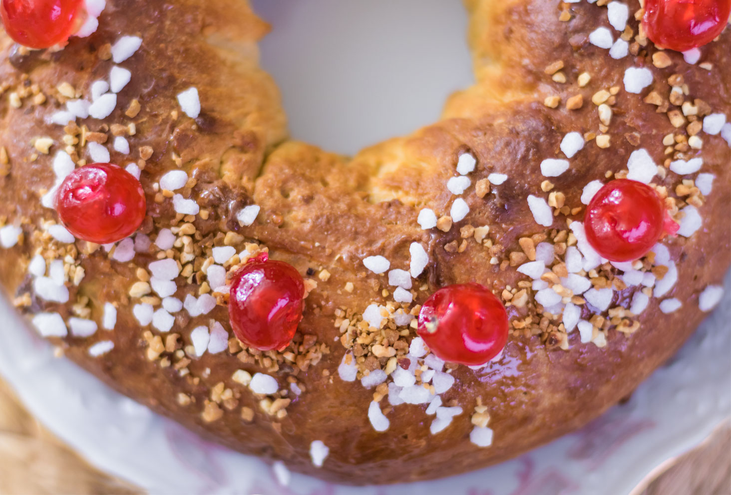 Zoom sur le dessus de la couronne des rois au beurre de cacahuètes avec ses éclats de pralin, ses perles de sucre et ses cerises confites