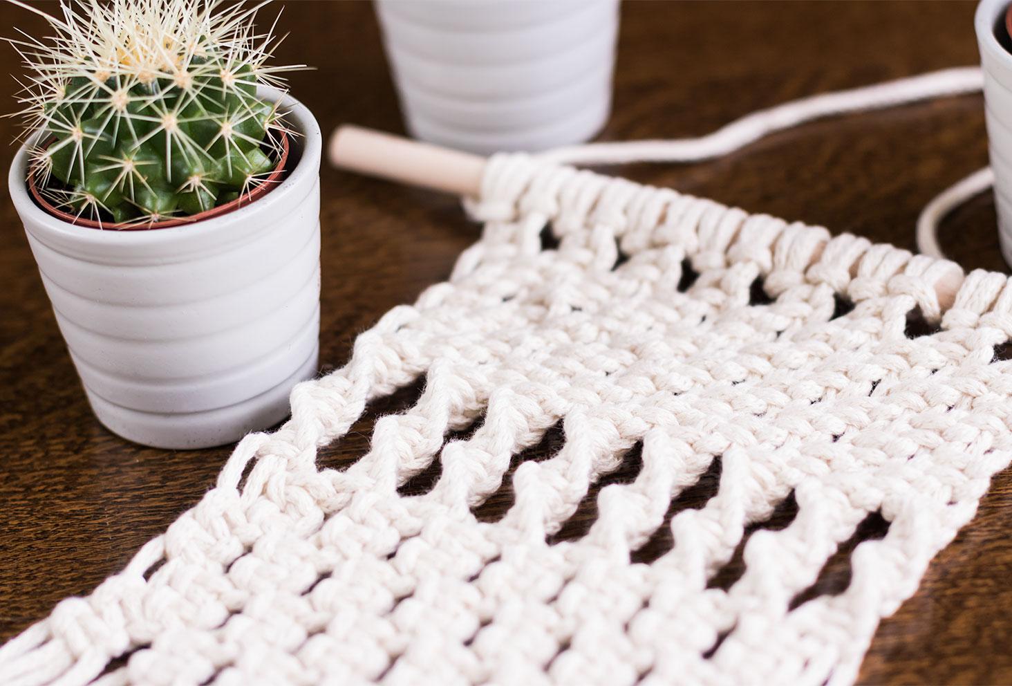 Zoom sur les noeuds demi plats d'un macramé beige sur la table en bois à coté d'un cactus