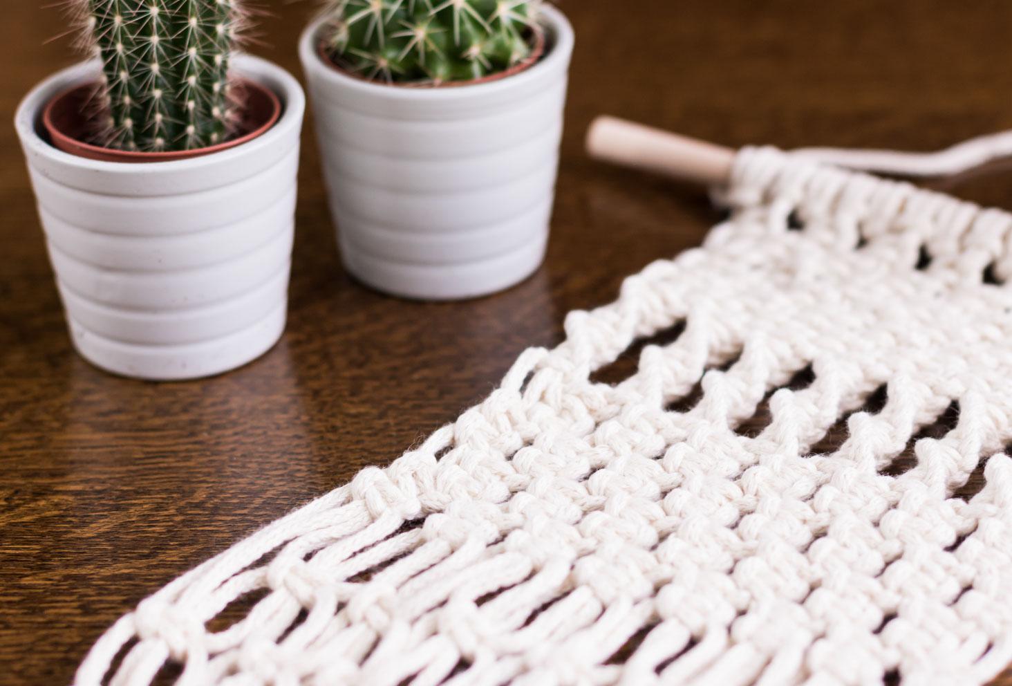 Zoom noeuds plats d'un macramé posé sur une table en bois entouré de minis cactus