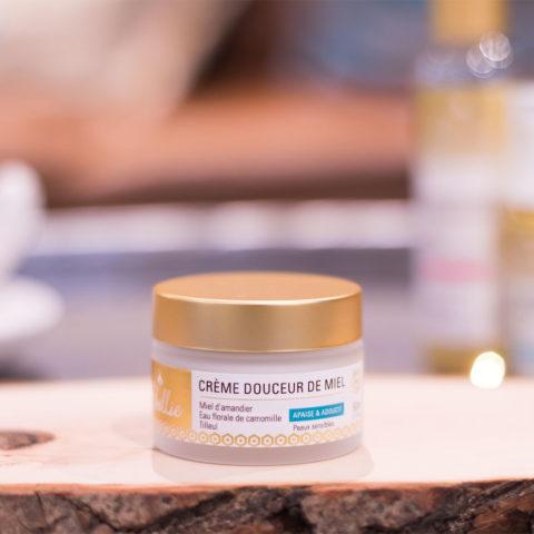 Zoom sur le packaging blanc et doré du pot de la crème Douceur de Miel par Abellie posé sur une tranche de bois
