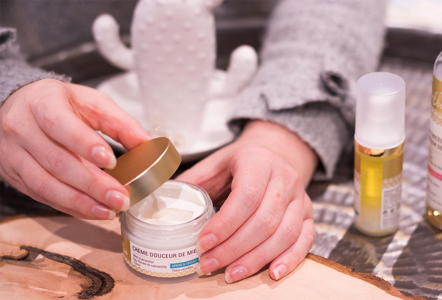 Zoom sur l'ouverture du pot doré de la crème Douceur de Miel par Abellie