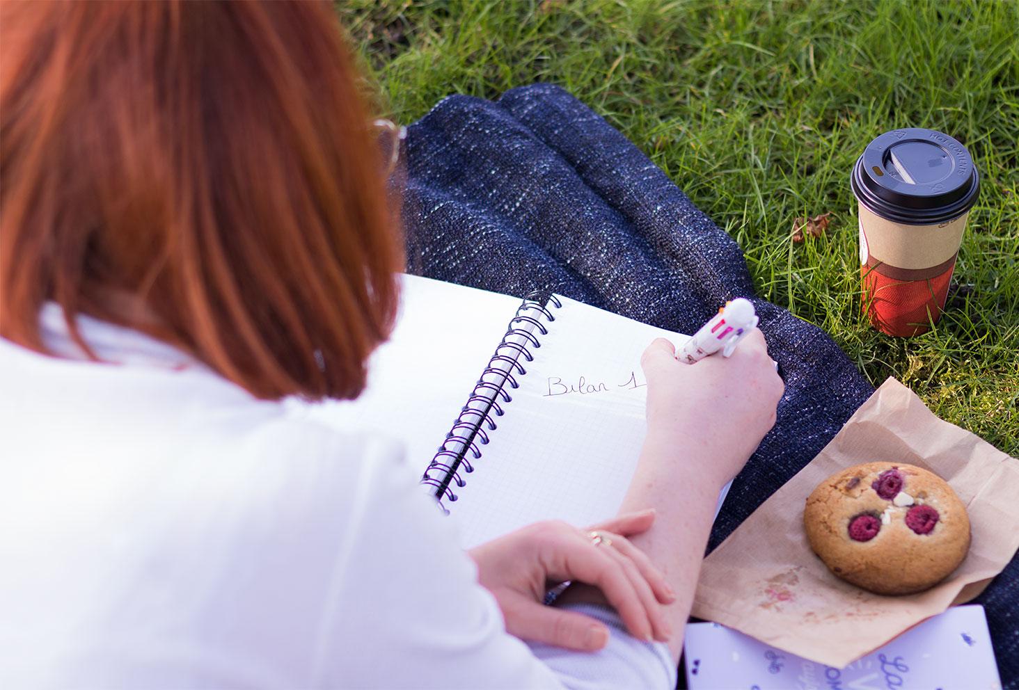 """L'inscription """"bilan 1"""" écrit sur un carnet ouvert dans l'herbe sur un plaid avec un cookie et un chocolat chaud"""