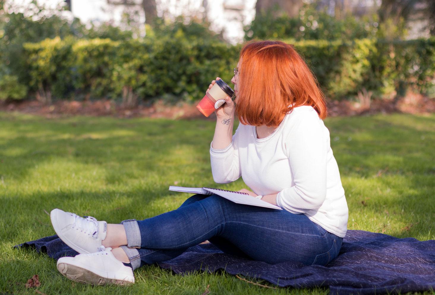 Assise au soleil sur un plaid dans l'herbe avec un café et un carnet ouvert sur les genoux