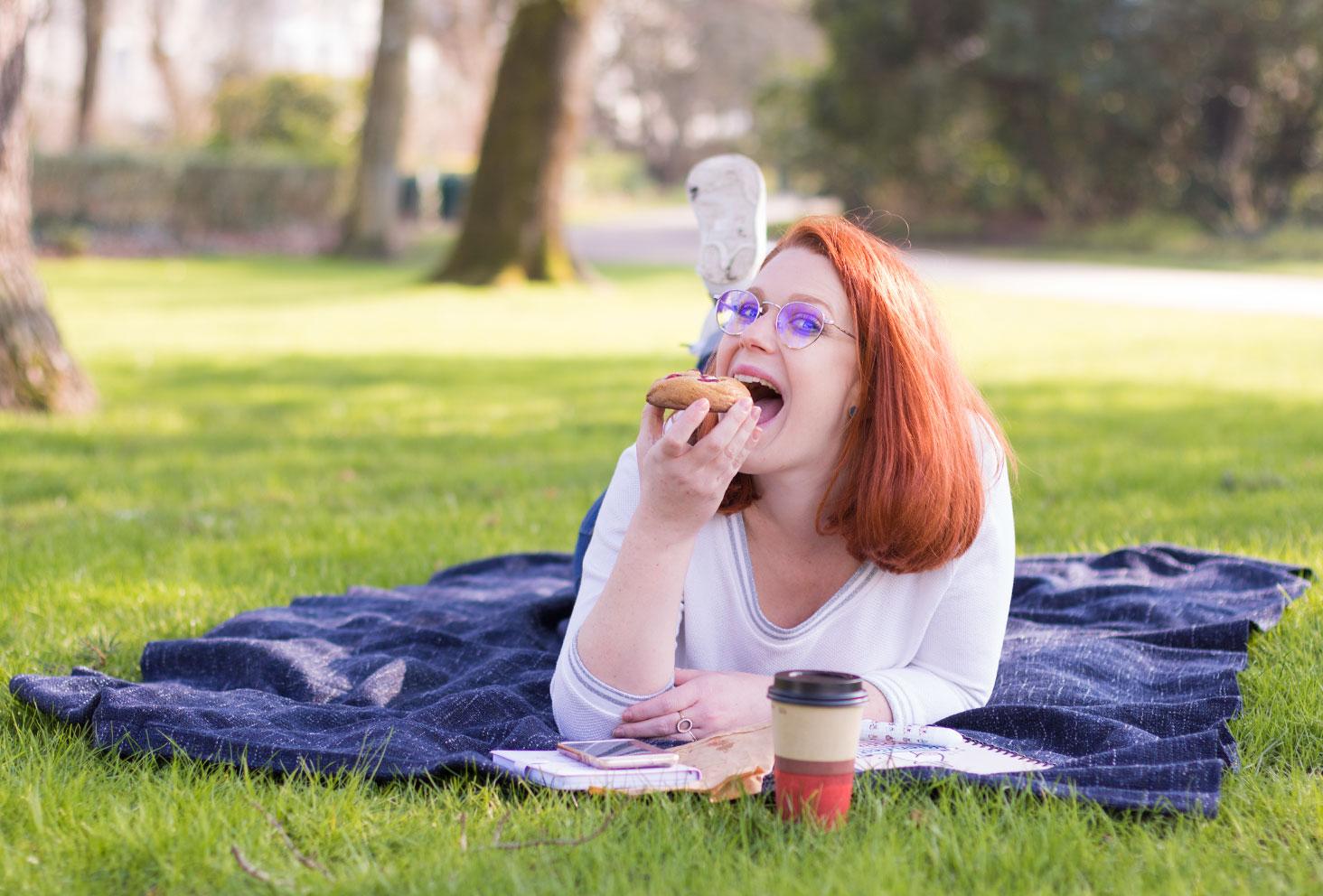 Entrain de manger un cookie chocolat blanc et framboise allongé dans l'herbe verte devant le salon de thé Quand Julie Pâtisse