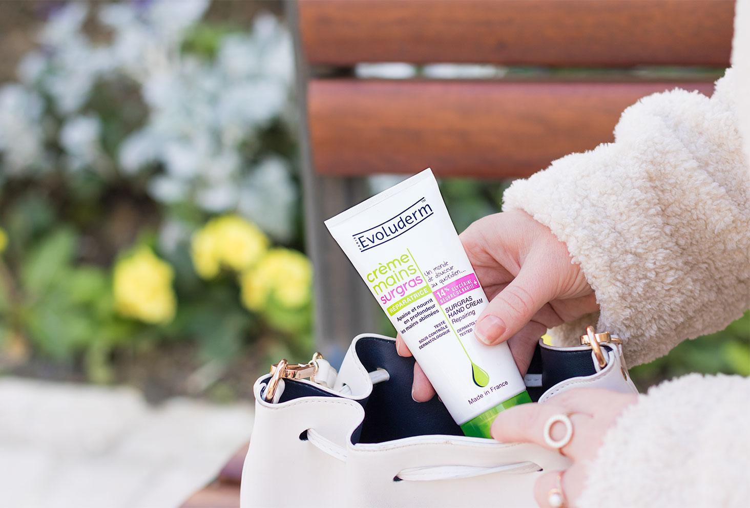 Packaging de la crème mains surgras Evoluderm sortie d'un sac à mains blanc sur un banc