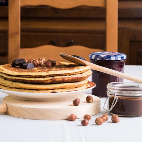 Crêpes et pâte à tartiner maison sur une table grise entouré d'éléments en bois et d'une confiture maison également