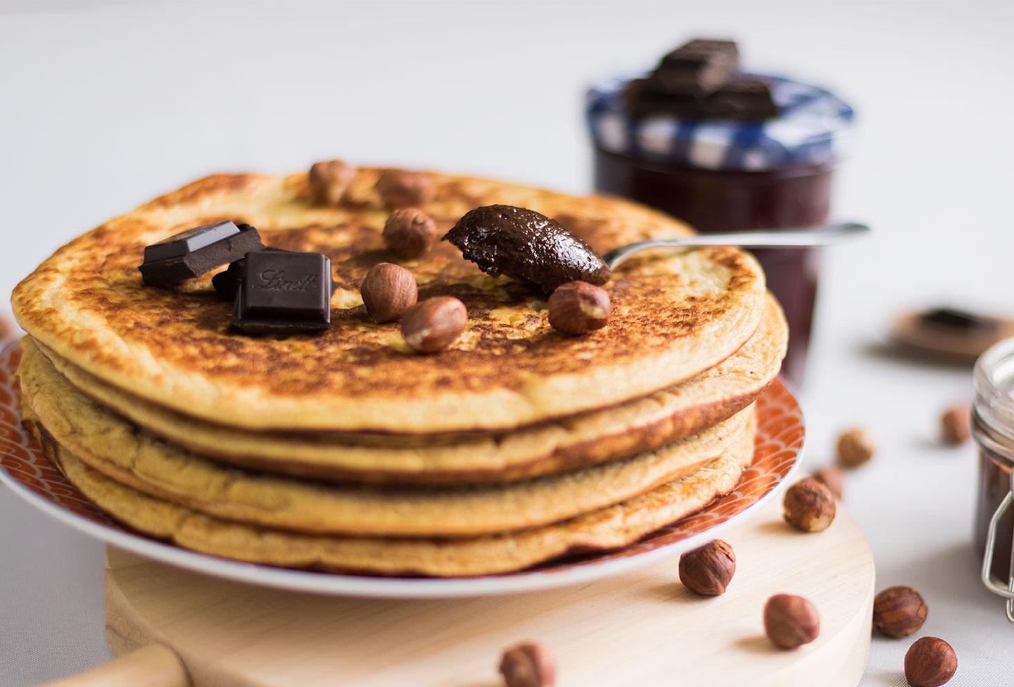 Crêpe épaisses maison ressemblant à des pancakes, recouvertes de noisettes entières et carreaux de chocolat